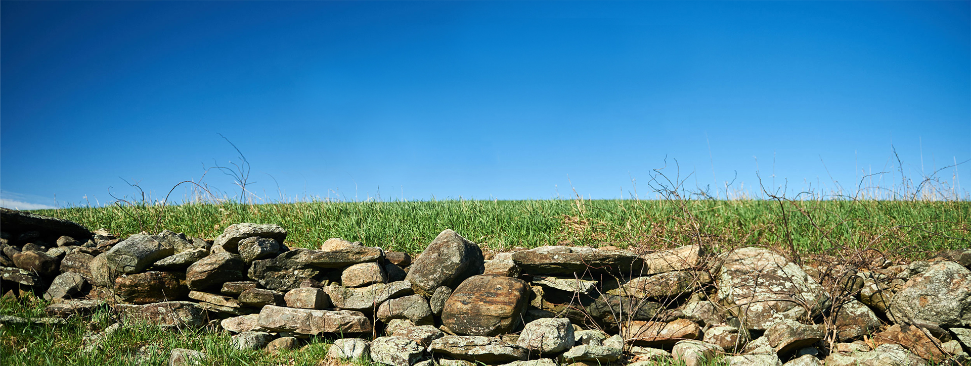 A stone wall in a wide-open field on a sunny day.
